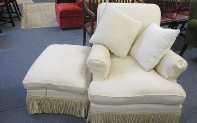 A late 20th century cream armchair with matching pouffe havi...