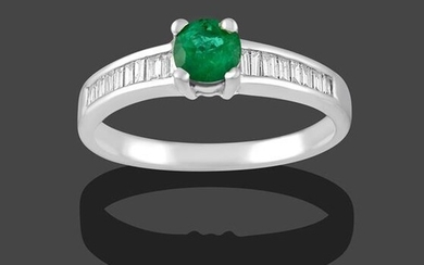 An Emerald and Diamond Ring, the round cut emerald in...