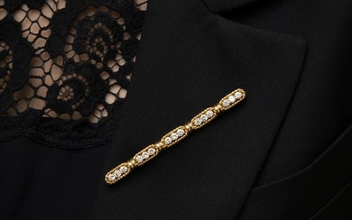 BARRETTE DIAMANTS A diamond and gold bar-brooch.