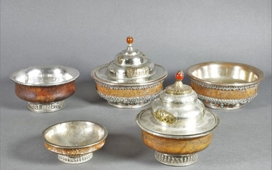 Set of five containers comprising: two covered wooden bowls with a silver metal frame. H. 10.5 and 11 cm; two wooden bowls with silver metal mounting and turquoise and coral inlays. D. 11.5 and 11.6 cm; one wooden bowl with silver-plated metal frame...
