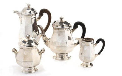 Silver plated metal tea/coffee set composed of four pieces including: a coffee pot, a teapot, a milk jug and a covered sugar bowl. Octagonal in shape, resting on round bases edged with fillets. Blackened wooden handles.