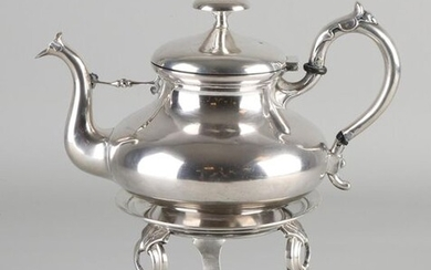 Silver teapot with comfort, 833/000. Tea pot bulbous model, with acanthus leaf on the handle and a decoration on the spout. MT .: Van Kempen, Voorschoten, jl.:n:1872, handle is a bit loose and various repair spots on the bottom of the jug. Placed on a...