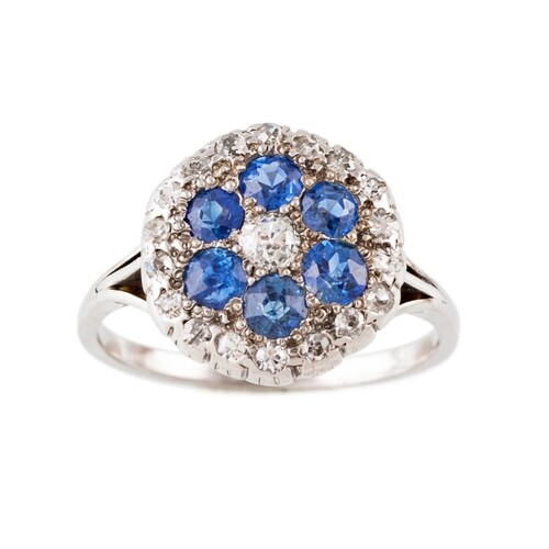 A DIAMOND AND SAPPHIRE CLUSTER RING, of circular for, mounte...