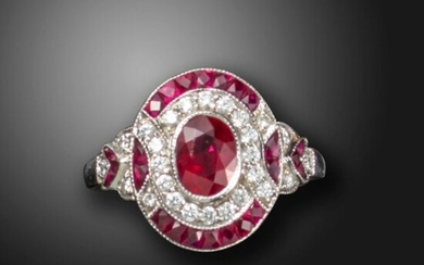 A ruby and diamond cluster ring, centred with an oval-shaped ruby within a surround of round brilliant-cut diamonds and French-cut rubies, with further rubies and diamonds to the shoulders in platinum, size N