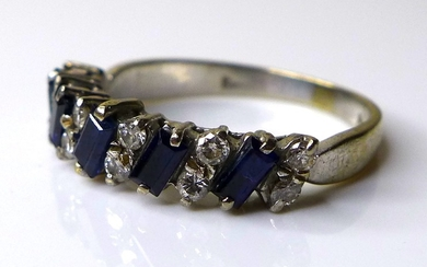 An 18ct white gold, dark sapphire and diamond ring, five bag...