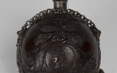 An early 19th century finely carved coconut bugbear powder flask of Napoleonic interest, one end typ