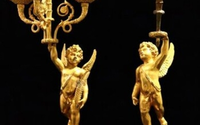 Pair of gilt bronze candelabra, each featuring a cherub on a guilloche base, standing on one foot, holding in its raised hand a horn with lights.