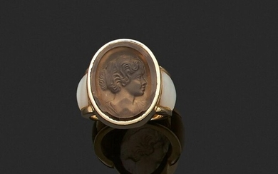 RING in yellow gold 750 thousandths, decorated with an engraved stone showing a woman in profile bust, between two mother-of-pearl motifs. Finger size : 52. Gross weight: 14.4 g. (traces of glue). Yellow gold ring decorated with an engraved stone...