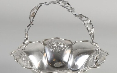 Silver bonbon basket, 934/000, octagonal model with floral decoration with brace-shaped edge and a handle of wire with leaf decoration. The basket is placed on a square base made of acanthus leaves and 4 curled legs. MT .: JGMeijer, and HW van Riel...