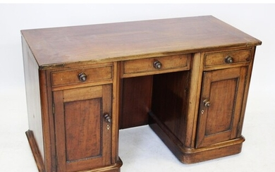 A Victorian mahogany kneehole desk/dressing table, the cleat...