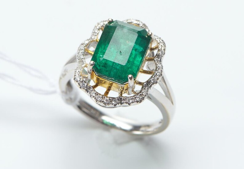 A ZAMBIAN EMERALD AND DIAMOND RING IN 18CT TWO TONE GOLD, THE EMERALD WEIGHING 4.71CTS, AND THE DIAMONDS TOTALING 0.13CTS, RING SI...