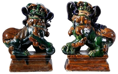 A pair of Tang-style sancai-glazed pottery Chinese guardian lions. Engraved...