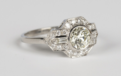 A platinum and diamond ring, collet set with the principal circular cut diamond within a shaped surr