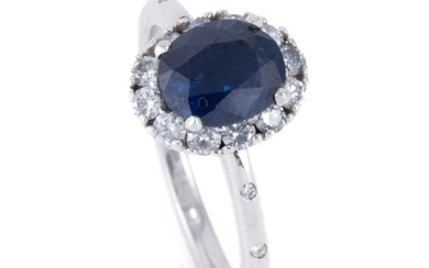 AN 18CT WHITE GOLD SAPPHIRE AND DIAMOND RING; featuring an oval cut mid dark blue sapphire of approx. 1.65ct with a halo of 12 round...