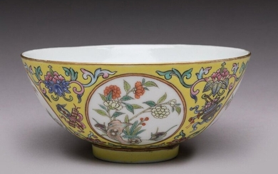 CHINA - DAOGUANG Period (1821 - 1850) Small porcelain bowl decorated with polychrome enamels of peonies, lingzhi and rocks in medallions, on a yellow background decorated with lotus in their foliage and auspicious objects tied with ribbons. On the...