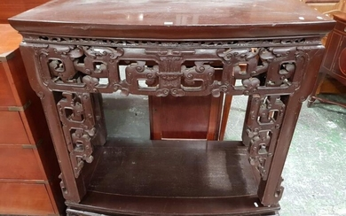 Chinese Bow Front Side Table, the apron carved in archaic style with stylised animals, raised on a separate conforming low platform...