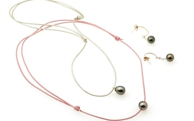 Lot comprising : Adjustable pink leather necklace, decorated with a tahitian pearl. Silver leather necklace, holding a Tahitian pearl. Pair of half crèole in silver 800/°° retaining a Tahitian pearl. Gross weight : 2.3g