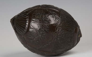 A 19th century carved coconut bugbear powder flask, one end typically worked with a mask with inset