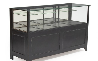 A French 20th century black painted wood counter, front, sides and top with thick glass. H. 91. L. 150. W. 54 cm.