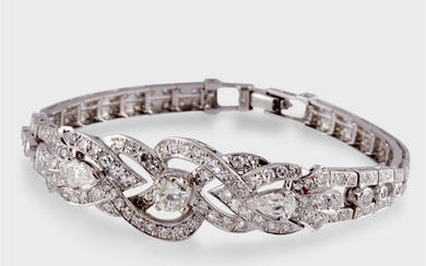 A diamond and fourteen karat white gold strap bracelet...