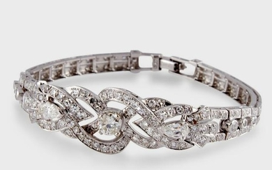 A diamond and fourteen karat white gold strap bracelet