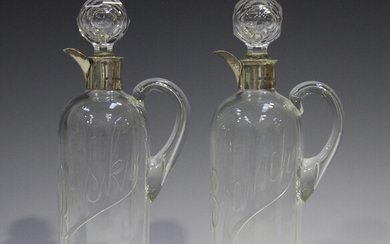 A pair of late Victorian silver mounted clear glass spirit flasks and stoppers, each cylindrical bod
