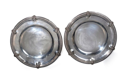 A pair of round silver dishes.