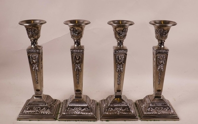 A set of four silver plate candlesticks on tapered plinths w...