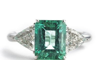 An emerald and diamond ring set with an emerald-cut emerald weighing app. 3.11 ct. flanked by two trilliant-cut diamonds, mounted in 18k white gold. Size 55.