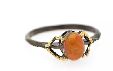 An opal ring set with an opal cabochon, mounted in black rhodium and gold plated sterling silver. Size 59.
