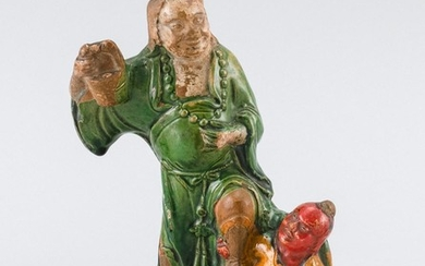 CHINESE POTTERY FIGURE GROUP In the form of a sennin in green robes subduing a red-faced demon. Marbled calligraphy on back. Height...