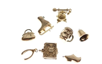 Eight assorted gold and yellow metal charms, 17g gross...