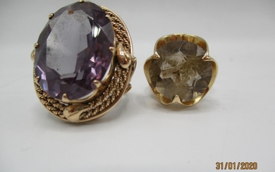 Two gold coloured metal rings, one set with a purple stone a...