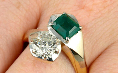 An emerald and brilliant-cut diamond two-stone crossover ring.