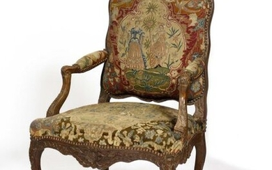 Beautiful richly carved beechwood armchair with flat back, decorated with leafy cartouches, rocailles and radiating motifs, upholstered with a tapestry with elegant decorations on the back. Louis XV style. Height 100 cm, width 73 cm, depth 60 cm.