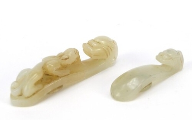 Two Chinese white jade belt hooks carved with dragons, the l...
