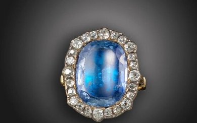 A sapphire and diamond cluster ring, centred with a cushion-shaped sapphire within a surround of graduated old cushion-shaped diamonds, in foil-back closed setting in silver on gold, with lobed decoration the reverse and scroll decoration to the gold...