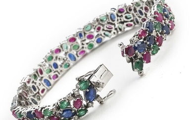 """A sapphire, ruby, emerald and diamond bracelet """"Tutti Frutti"""" set with numerous sapphires, rubies, emeralds and diamonds, mounted in 14k white gold."""