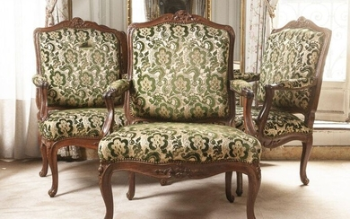 A suite of three armchairs à la reine in moulded and carved natural wood with flower decoration. Moving backrest, whiplash armrest supports, curved legs.