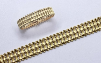Articulated bracelet in gold 750 thousandths, composed of links with bamboo decoration. It is embellished with a ratchet clasp with eight safety clasps.