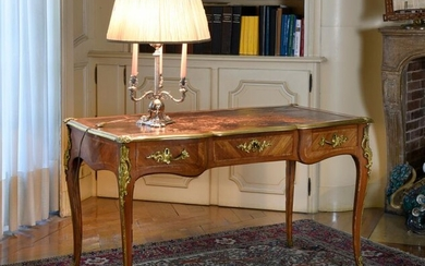 Flat, curved, middle desk in violet and rose veneer wood with rectangular reserves, opening at the top by three drawers, with a scrolled top surrounded by a moulded ingot mould with corner clips, trimmed with central leather, rests on curved legs.