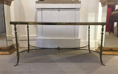 MAISON JANSEN (attributed to) Rectangular gilded brass coffee table with bamboo imitation legs joined by a moving X-shaped spacer bar. Top with a mirrored eglomised bottom. 20th century. Height : 46,5cm Width : 95,5cm Depth : 54cm