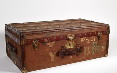 Maison Moynat Fabricant, 5 place du théâtre français, Paris . Travel trunk in coated canvas on wood core. Wooden reinforcements, brass rivets and locks. Inside a red leather pocket. H:32 W:86 D:51 cm. Slight wear and tear
