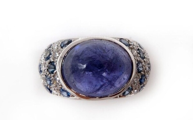 RING in 18K white gold holding a 5.60 carat tanzanite cabochon in a surround of sapphires and pavé diamonds. French work. TDD: 51. Gross weight : 10.90 gr. A 5.60 carats tanzanite, sapphire, diamond and gold ring.