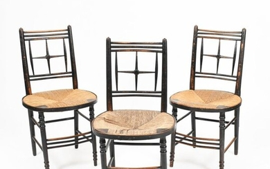 Three Morris & Co Sussex ebonised wood chairs, possibly designed by Ford Maddox Brown, each with slightly curved backs, set with turned, cross back splat design, circular rush seat, on turned leg and stretchers, unsigned, 84.5cm. high, (3) Provenance...
