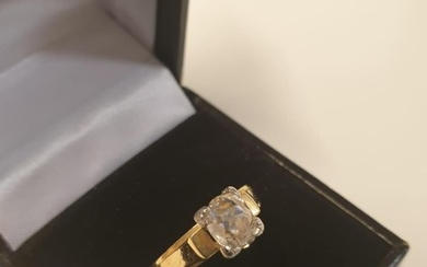 Yellow metal diamond solitaire ring with cushion cut stone o...