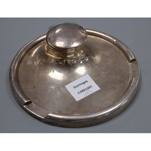 A George V silver circular inkwell, the rim with pen recess,...