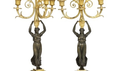 A pair of French Empire gilt and patinated bronze candelabra. Early 19th century. H. 65 cm. (2)