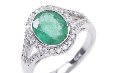 AN EMERALD AND DIAMOND CLUSTER RING - Of Art Deco design, featuring an oval cut emerald estimated 2.20cts, in a surround of round br...