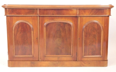 Mahogany sideboard, varnished in buff, opening by three doors and...